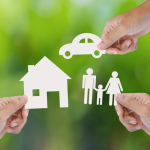 Hands holding paper house, car and family
